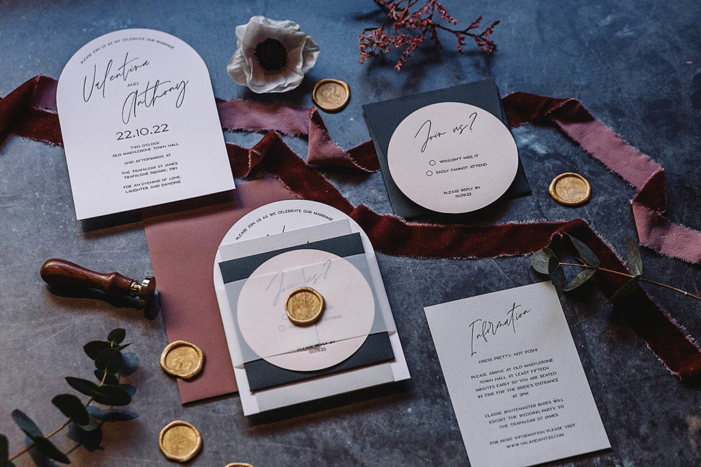 Luxury wedding invitation suite featuring arch shaped invitations with modern calligraphy, blush envelopes and gold wax seals