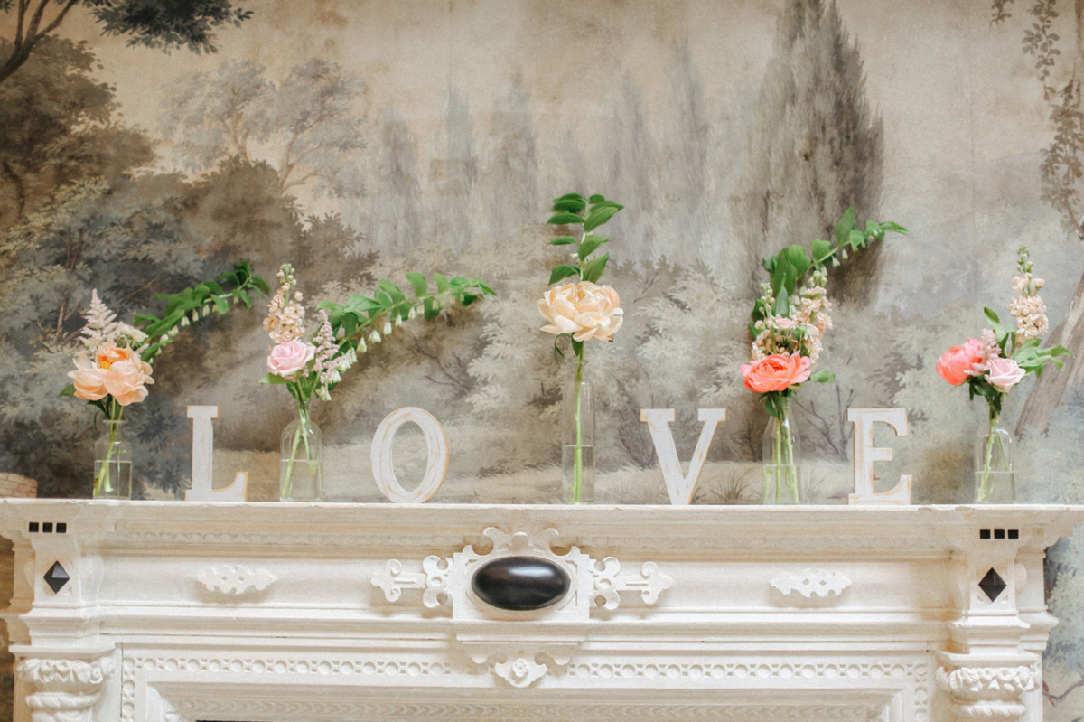 Single stem peach flowers in glass vases with LOVE letters - A Caroline Castigliano Gown for a Chic and Classic Manor House Wedding in Shades of Peach